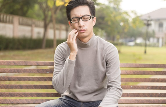 Man sitting at a park bench massaging his cheek to alleviate pain from his recent orthodontic treatment.